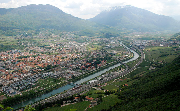 Grad leži na rijeci Adiđe u kotlini ispod Alpskih Dolomita